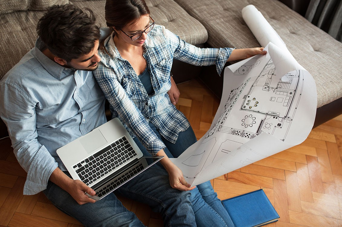 A couple sitting on the floor in front of the couch, the man holds a laptop, the woman holds a set of blueprints for the house. The man has his arm around the woman's waist as they both look at the blueprints inquisitively.
